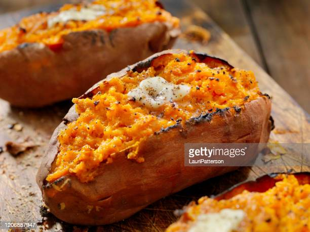 twice baked, stuffed sweet potatoes with melting butter and cracked pepper - yam stock pictures, royalty-free photos & images