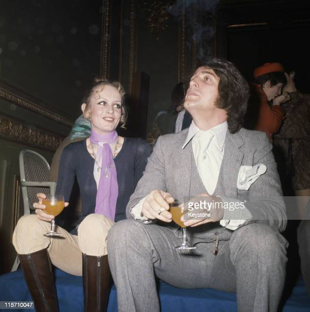 Twiggy and her manager and boyfriend Justin de Villeneuve holding wine glasses while attending an event at the Ritz Hotel in London England Great...