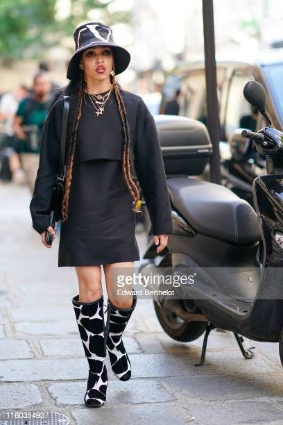 Twigs wears a Valentino hat a black dress necklace cow print black and white boots earrings outside Valentino during Paris Fashion Week Haute Couture...