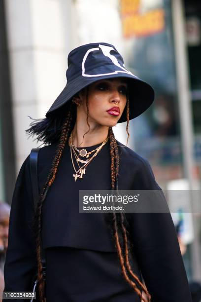 Twigs wears a Valentino hat, a black dress, necklace, earrings, outside Valentino, during Paris Fashion Week -Haute Couture Fall/Winter 2019/2020, on...