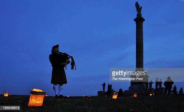 Twilight descends at Antietam National Battlefield's 23rd Annual Memorial Illumination as David Throne plays Amazing Grace on his bagpipe in...
