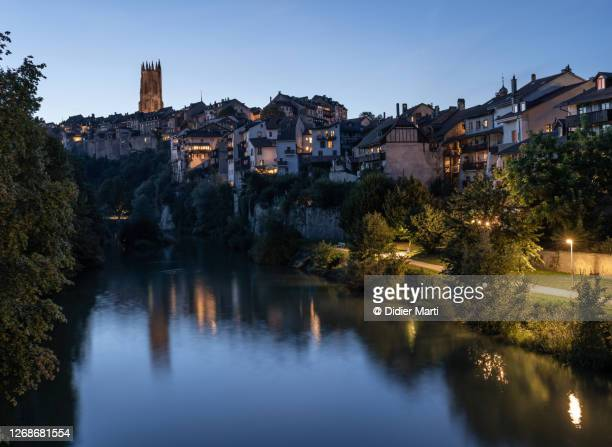 twilight over fribourg old town and the sarine river in switzerland - フリブール州 ストックフォトと画像