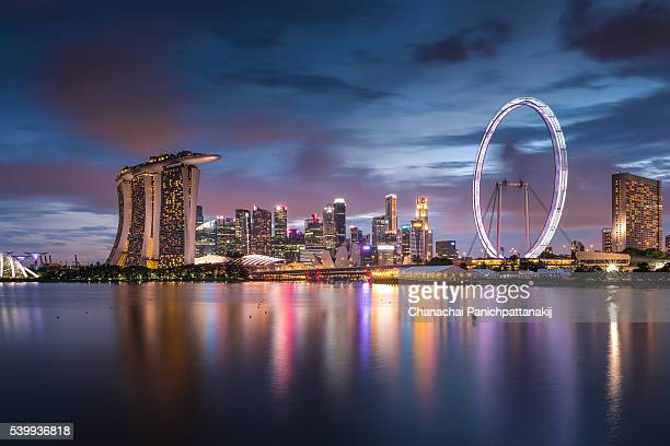 twilight scene of downtown city skyline in singapore - singapore flyer stock photos and pictures
