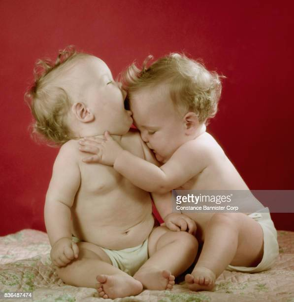 twin baby girls hugging - constance bannister stock photos and pictures