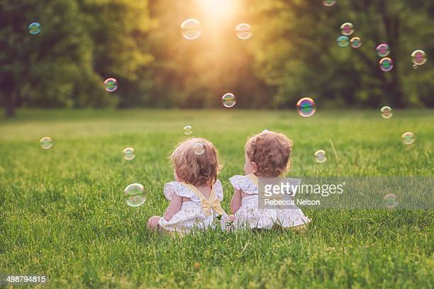 Twin baby girls surrounded by bubbles