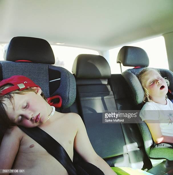Twin boy and girl (4-6) asleep in back of car