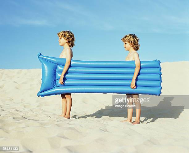 twin boys carrying an inflatable - symmetrie stockfoto's en -beelden