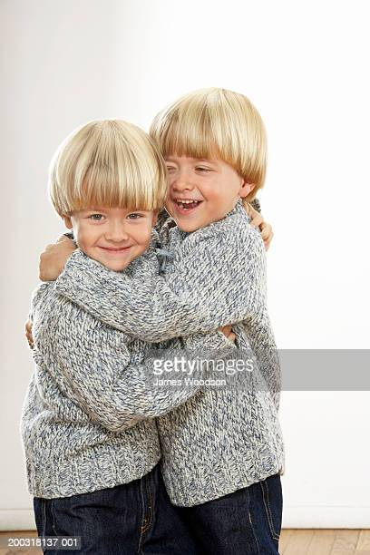 Twin boys (3-5) embracing, smiling and laughing, portrait