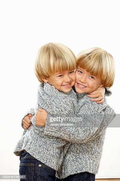 Twin boys (3-5) embracing, smiling, portrait