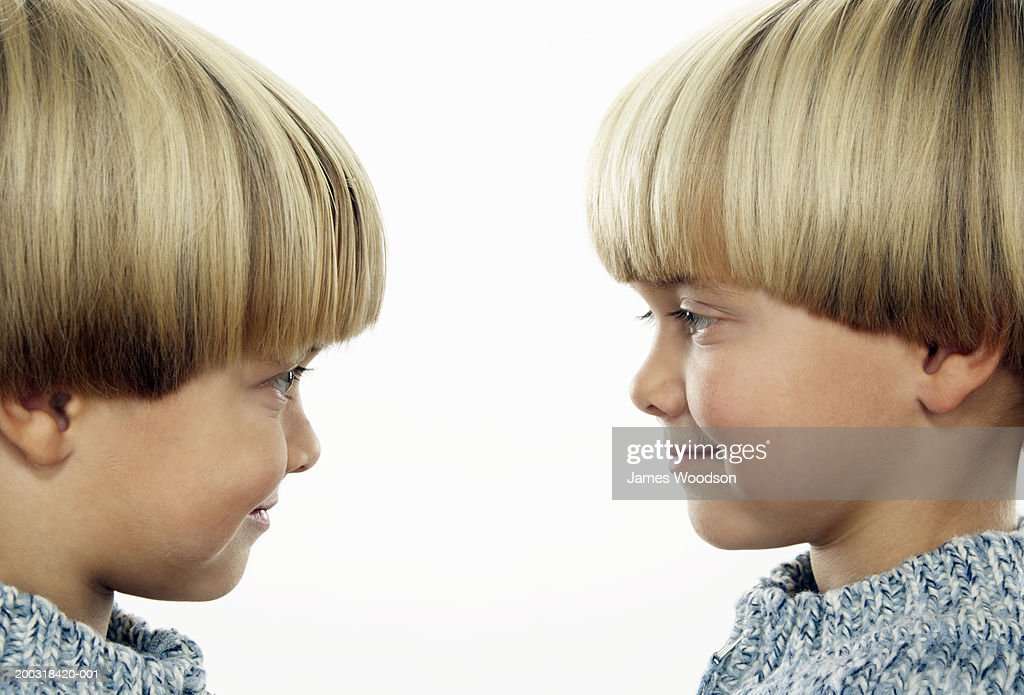 Twin boys (3-5) face to face, smiling, side view, close-up : Stock Photo