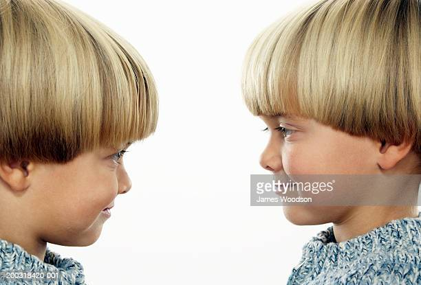 Twin boys (3-5) face to face, smiling, side view, close-up