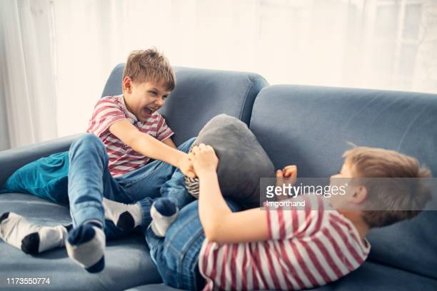 twin boys fighting at home - fighting stock pictures, royalty-free photos & images