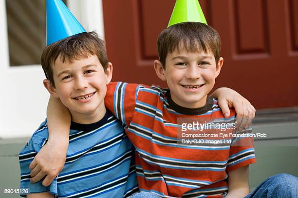 """twin boys in party hats and striped shirts - """"compassionate eye"""" stock pictures, royalty-free photos & images"""