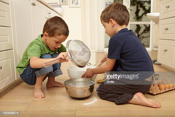 Twin boys making cake mix on the floor