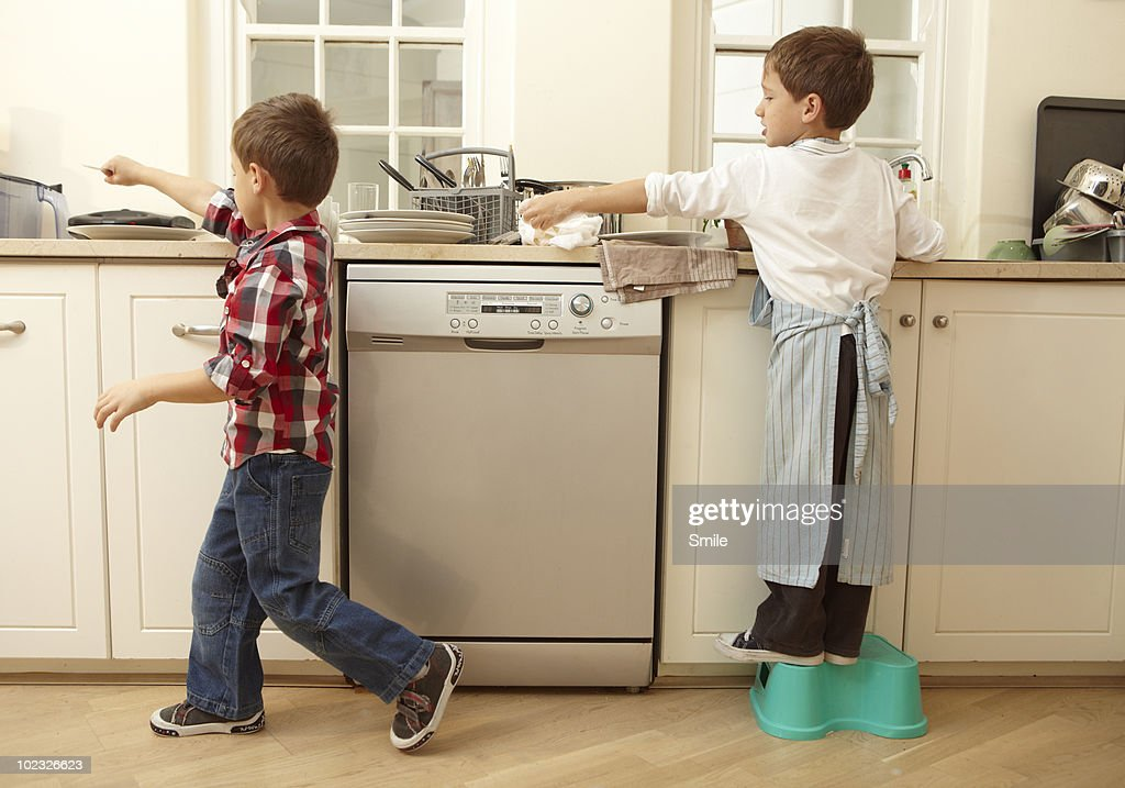 Twin boys passing cutlery while washing dishes : Stockfoto