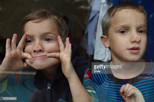 Twin boys pulling faces against window