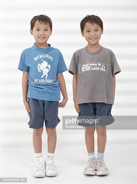 Twin boys (6-7) standing, smiling, portrait