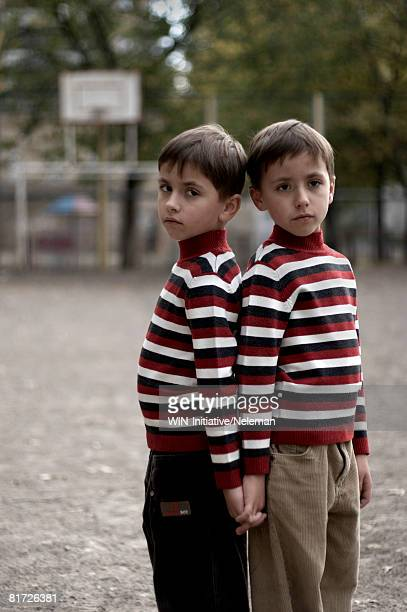 Twin boys standing together, back to back on playground, portrait