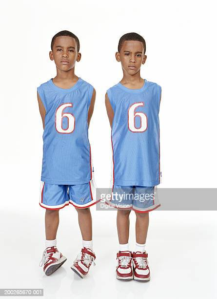 Twin boys (6-8) standing with hands behind backs, portrait
