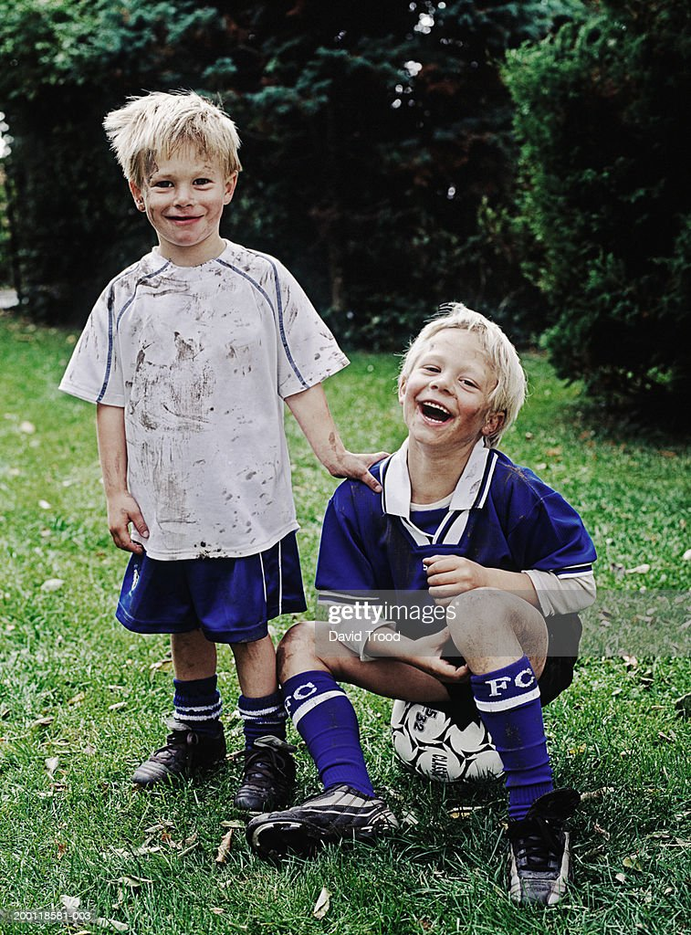 Twin boys (6-8) wearing football kits, one sitting on ball, portrait : Stock Photo
