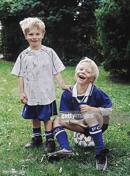 twin boys (6-8) wearing football kits, one sitting on ball, portrait - traje de fútbol fotografías e imágenes de stock