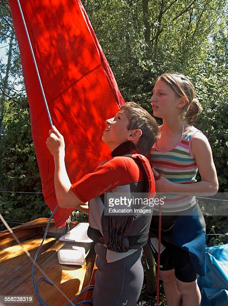 Twin brother and sister rigging the sails and mast on a mirror class sailing dinghy UK