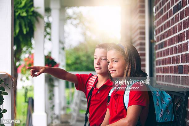 Twin brother and sister sitting on bench pointing, on first day of new school year