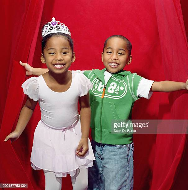 Twin brother and sister (5-7) smiling on stage in front of red curtain