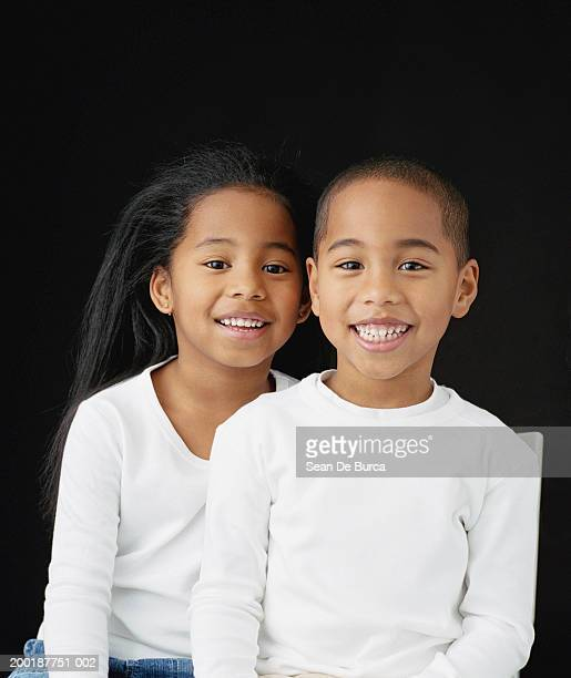 Twin brother and sister (5-7) smiling, portrait