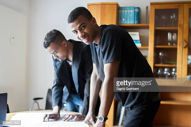 twin brothers at home, looking at documents - sigrid gombert stock-fotos und bilder