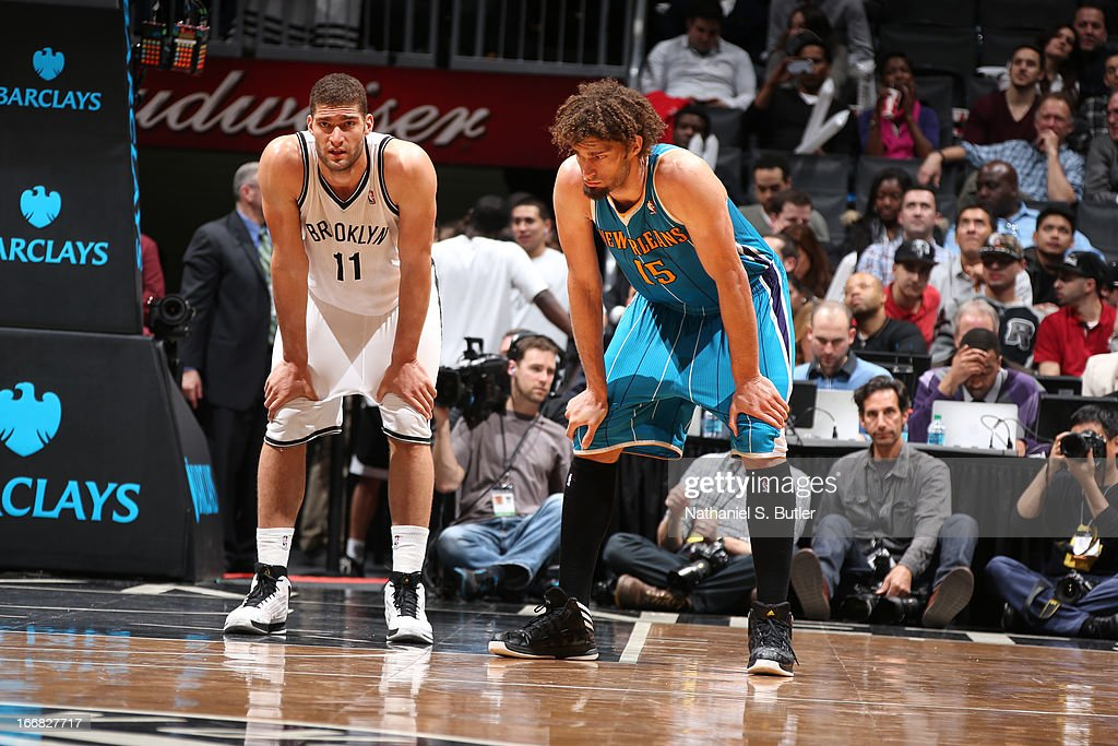 Twin brothers, Brook Lopez #11 of the Brooklyn Nets and Robin Lopez #15 of the New Orleans Hornets look on during a break in action on March 12, 2013 at the Barclays Center in the Brooklyn borough of New York City.