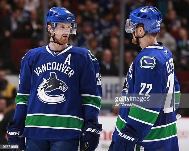 Twin brothers Daniel Sedin and Henrik Sedin of the Vancouver Canucks talk to each other during their game against the Nashville Predators at General...