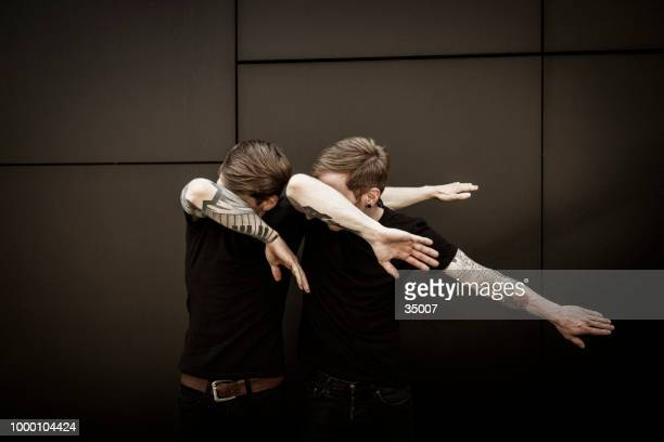 twin brothers doin the dab dance figure - human limb stock pictures, royalty-free photos & images