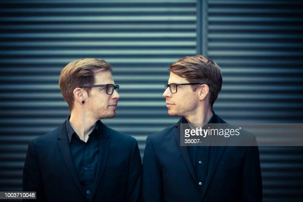 twin brothers face to face portrait - identity stock photos and pictures