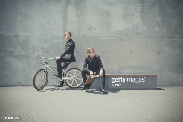 twin brothers in business outfit with bmx bike and skateboard - bmx cycling stock pictures, royalty-free photos & images