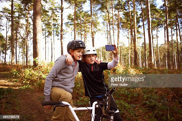 Twin brothers on BMX bikes taking self portrait