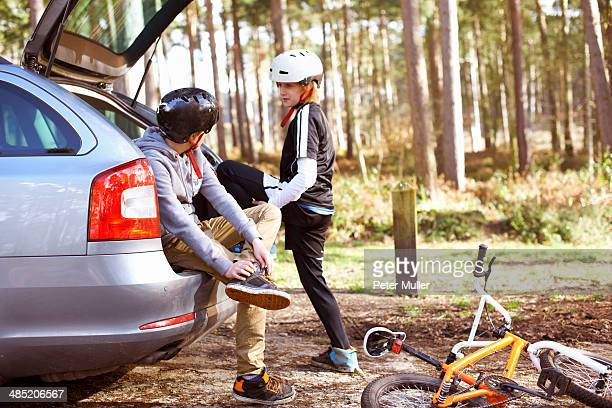 twin brothers preparing to ride bmx bikes in forest - safety equipment stock pictures, royalty-free photos & images