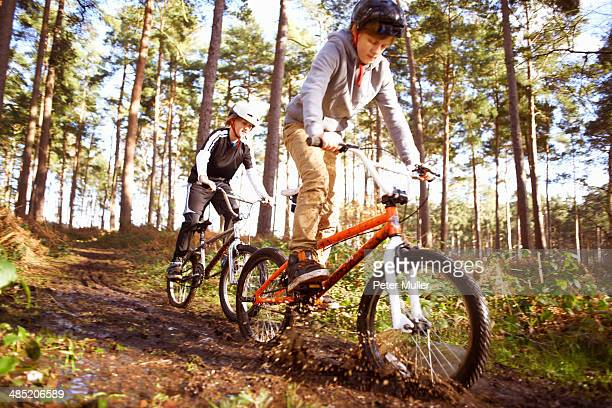 Twin brothers racing BMX bikes through muddy forest