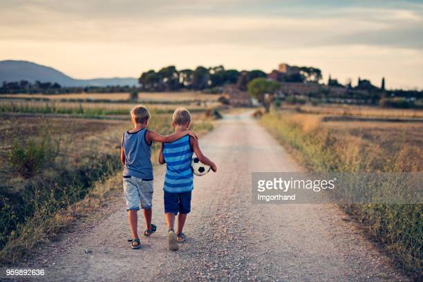 twin brothers returning home after playing soccer. - sport di squadra foto e immagini stock