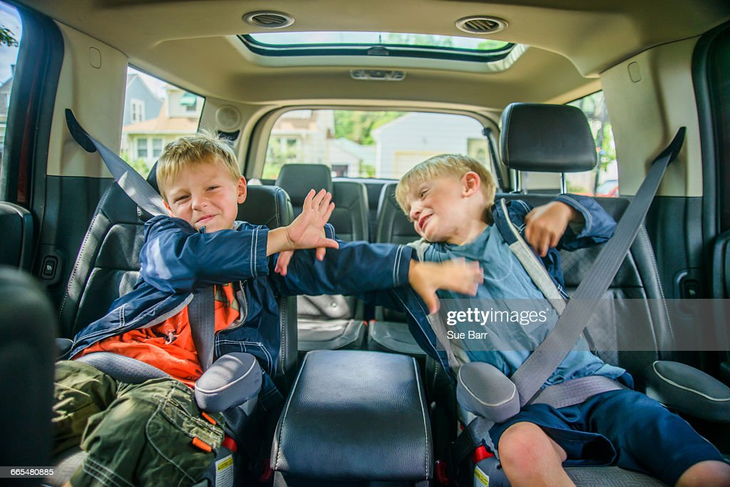 Twin brothers sitting in back of vehicle, fighting : Stock Photo