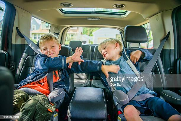 twin brothers sitting in back of vehicle, fighting - family inside car stock photos and pictures