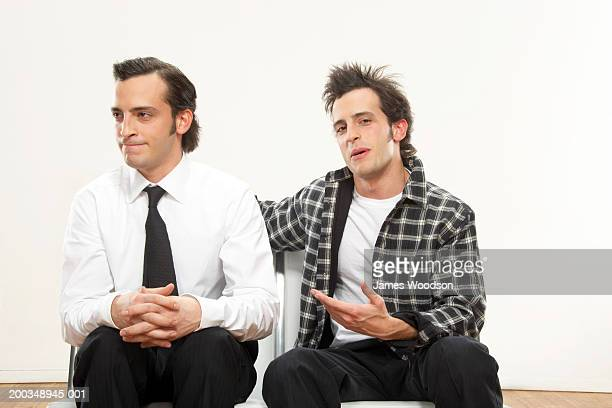 Twin brothers sitting side by side, one wearing suit