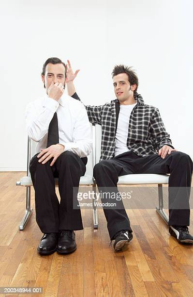 Twin brothers sitting side by side, one wearing suit, portrait