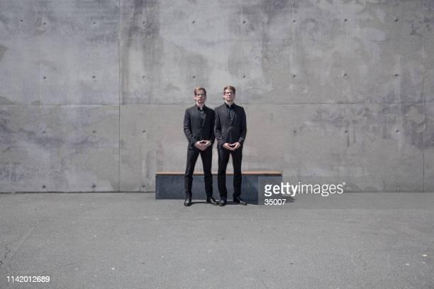 双子の兄弟が並んで立っている - 双子 ストックフォトと画像