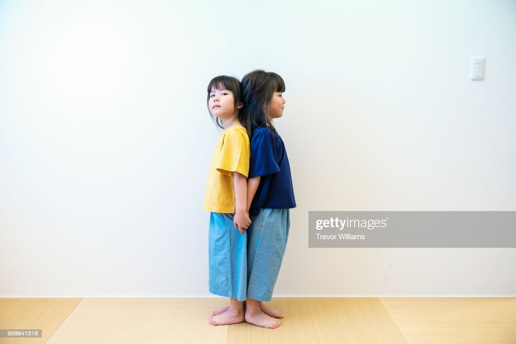 Twin girls comparing their height : Stock-Foto