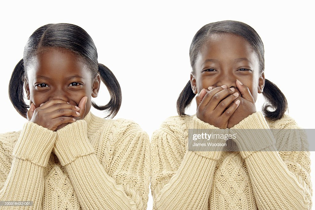 Twin girls (7-9) covering mouths with hands, portrait, close-up : Stock Photo