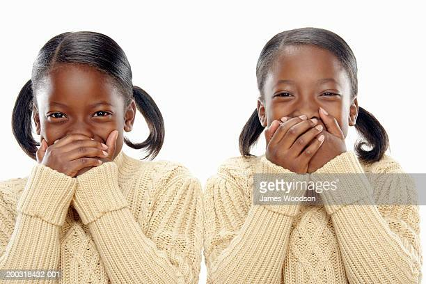 Twin girls (7-9) covering mouths with hands, portrait, close-up