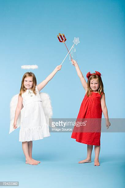 Twin girls dressed as an angel and devil