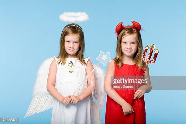 twin girls dressed as an angel and devil - devil stock pictures, royalty-free photos & images