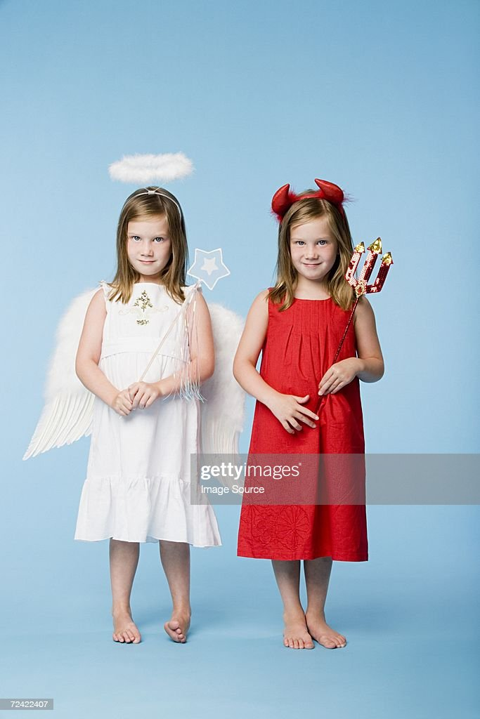 Twin girls dressed as an angel and devil : Stock Photo